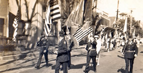 Men marching in uniform with American flags