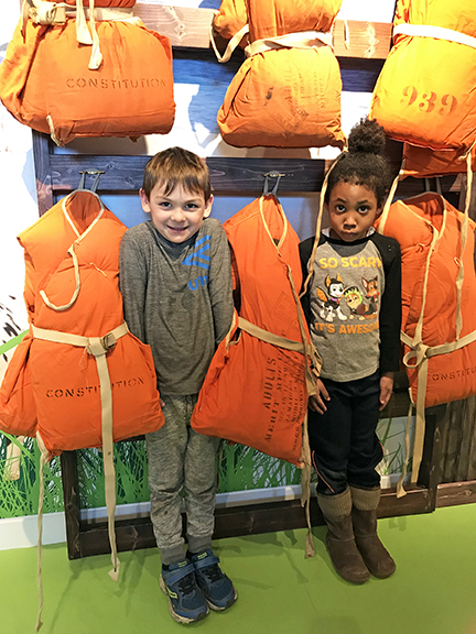 Kids standing near life jackets playfully